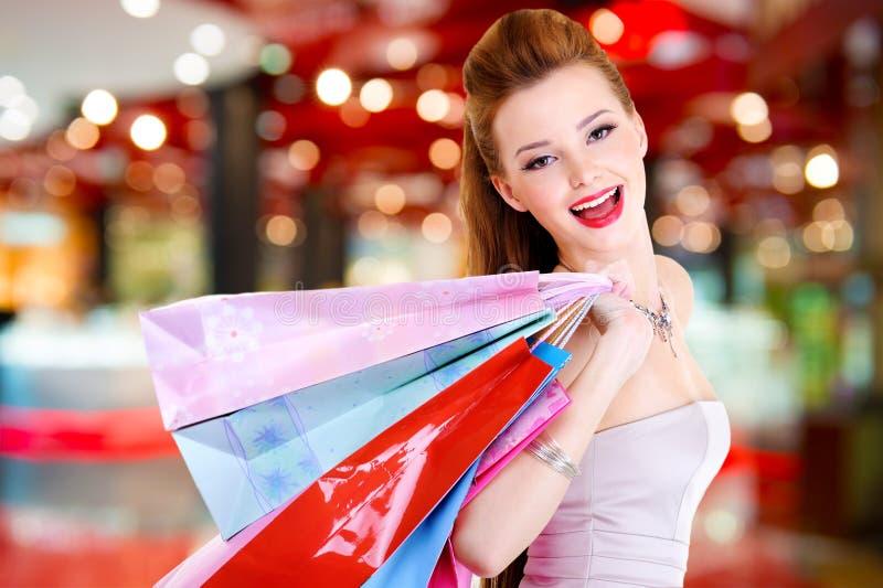 Γυναίκα με τις τσάντες αγορών στο κατάστημα στοκ φωτογραφία με δικαίωμα ελεύθερης χρήσης