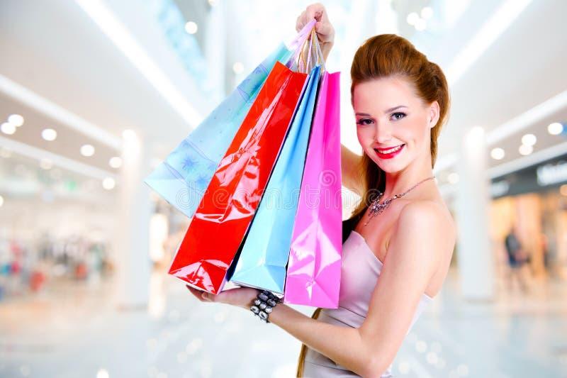 Γυναίκα με τις τσάντες αγορών στο κατάστημα στοκ εικόνα με δικαίωμα ελεύθερης χρήσης