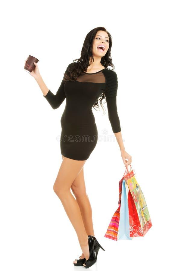 Γυναίκα με τις τσάντες και το φλιτζάνι του καφέ αγορών στοκ εικόνες