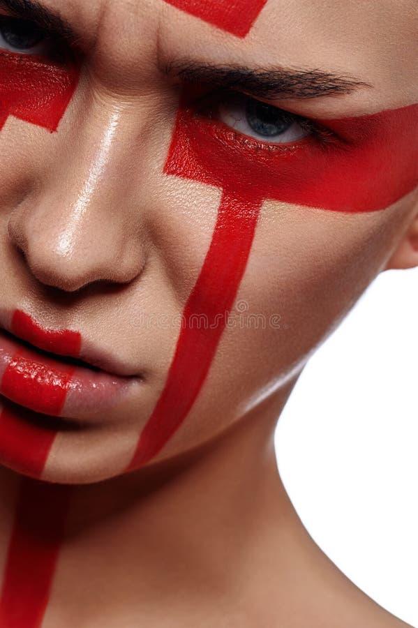 Γυναίκα με τις φυλετικές κόκκινες χρωματισμένες μορφές στο πρόσωπό της στοκ φωτογραφίες με δικαίωμα ελεύθερης χρήσης