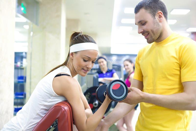 Γυναίκα με τον εκπαιδευτικό στη γυμναστική στοκ εικόνες