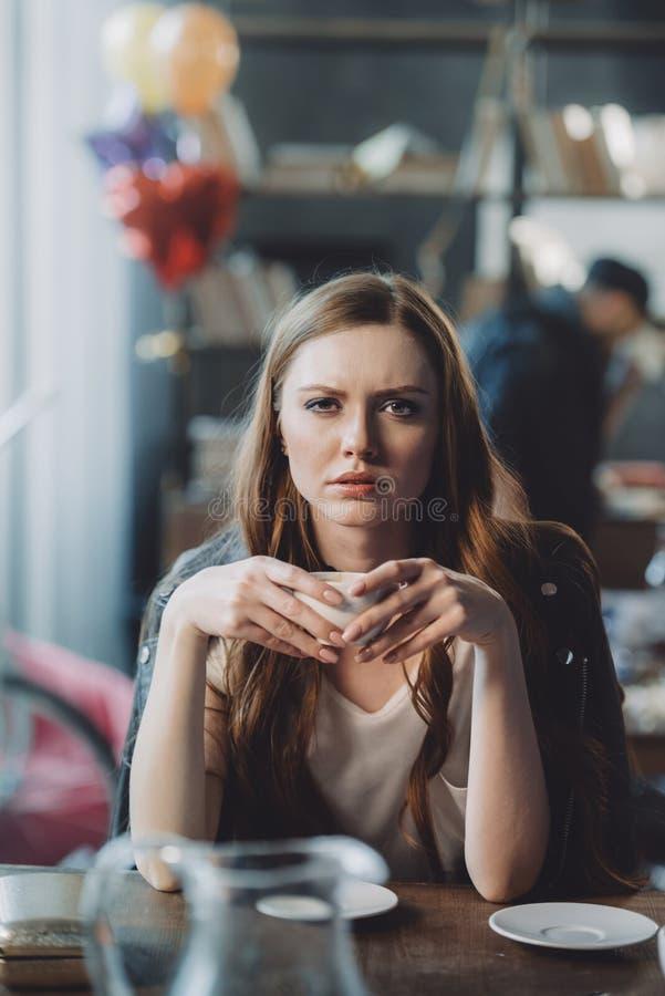 Γυναίκα με τον καφέ στο ακατάστατο δωμάτιο μετά από το κόμμα στοκ εικόνα με δικαίωμα ελεύθερης χρήσης