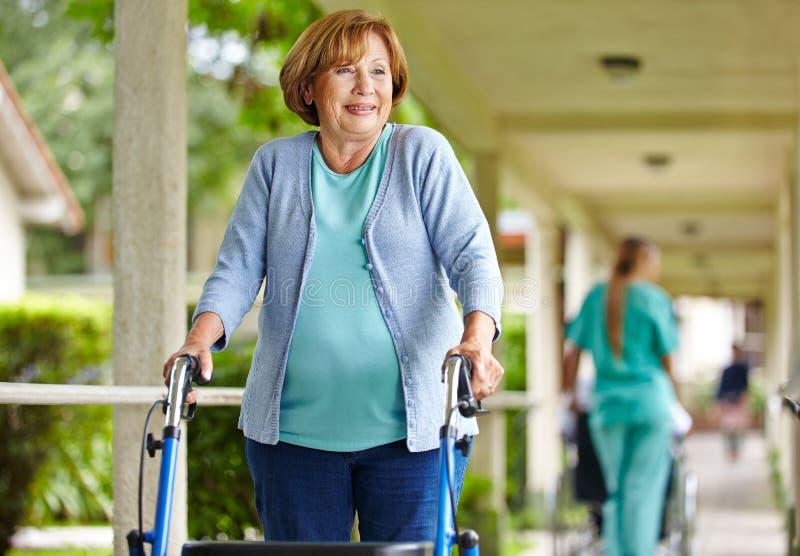 Γυναίκα με τον περιπατητή στη ιδιωτική κλινική στοκ φωτογραφία