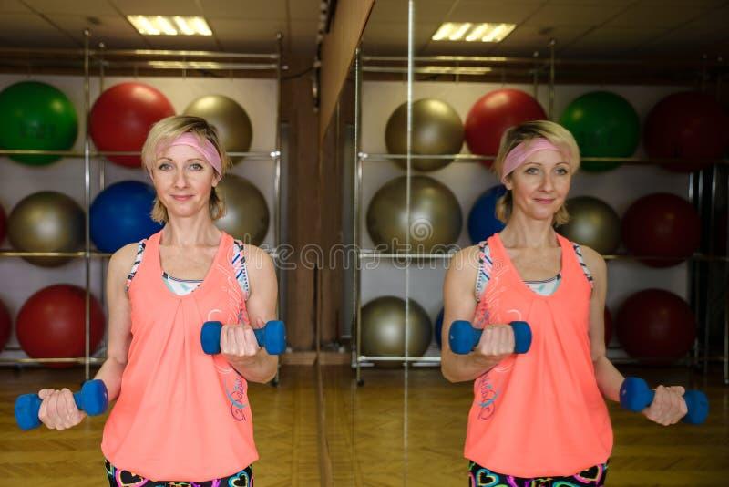 Γυναίκα με τους αλτήρες σε μια γυμναστική στοκ εικόνα