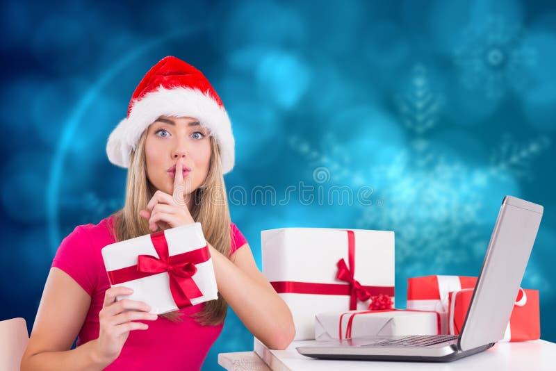 Γυναίκα με το δάχτυλο στο δώρο Χριστουγέννων χειλικής εκμετάλλευσης κατά τη διάρκεια του χρόνου Χριστουγέννων στοκ εικόνες