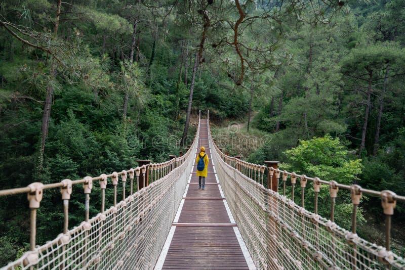 Γυναίκα με το αδιάβροχο walikng στη γέφυρα αναστολής στοκ εικόνα