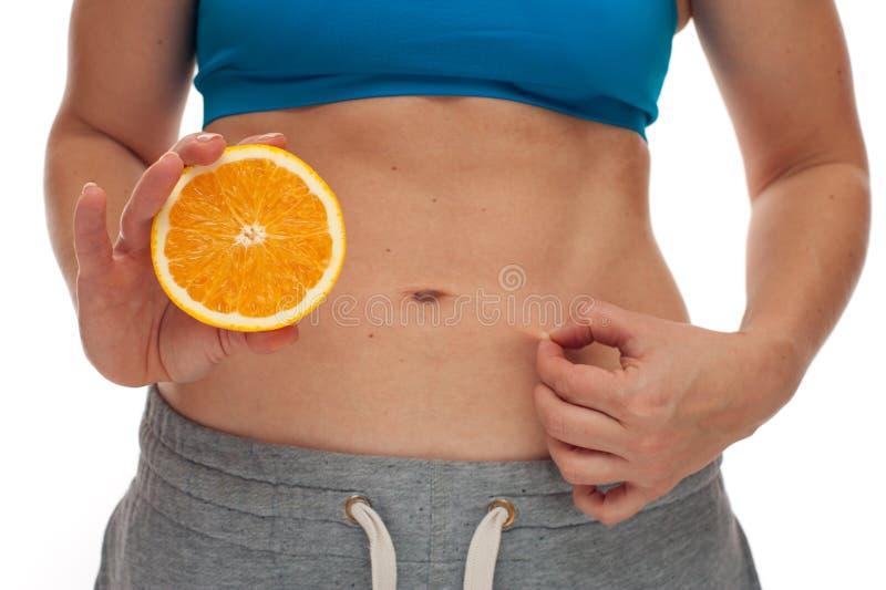 Γυναίκα με το αθλητικό σώμα που κρατά ένα φρέσκο μήλο στοκ εικόνες
