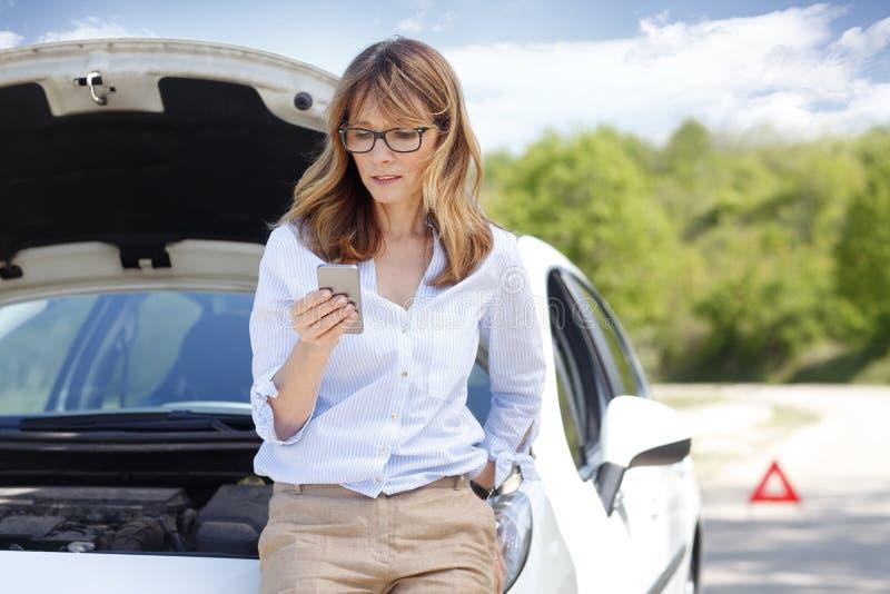 Γυναίκα με το αυτοκίνητο στο δρόμο στοκ φωτογραφίες