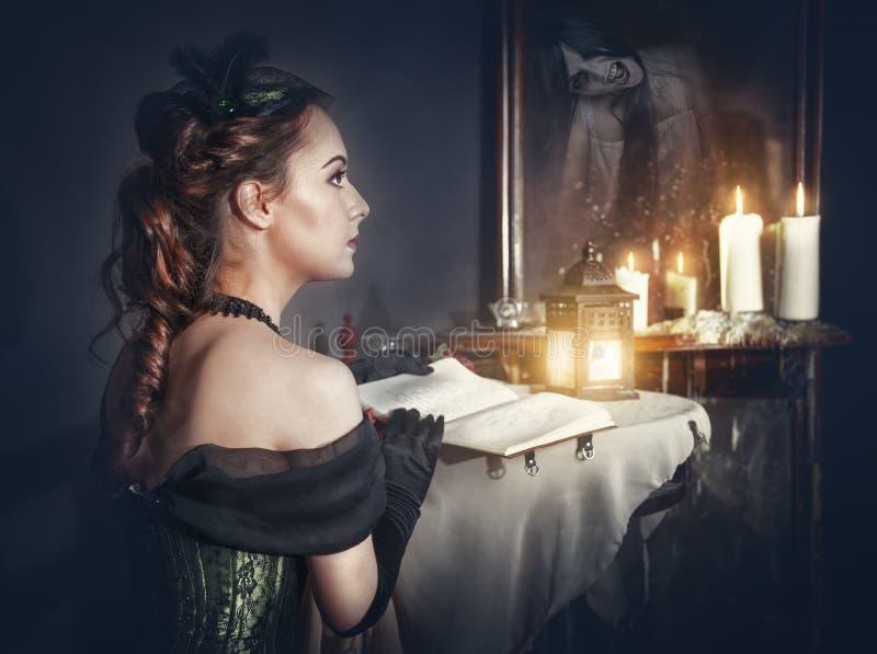 Γυναίκα με το βιβλίο στο αναδρομικό φόρεμα και το φάντασμα στον καθρέφτη στοκ εικόνες