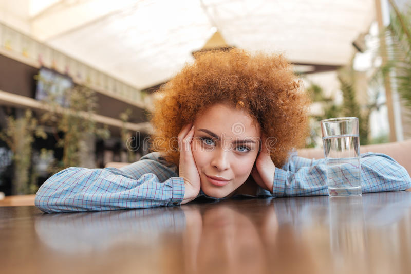 Γυναίκα με το γυαλί της συνεδρίασης και της χαλάρωσης νερού στον καφέ στοκ φωτογραφία