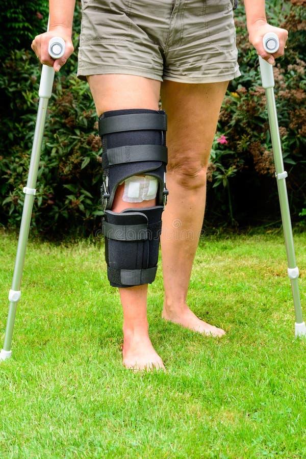 Γυναίκα με το γόνατο στο στήριγμα μετά από τον τραυματισμό στοκ εικόνα