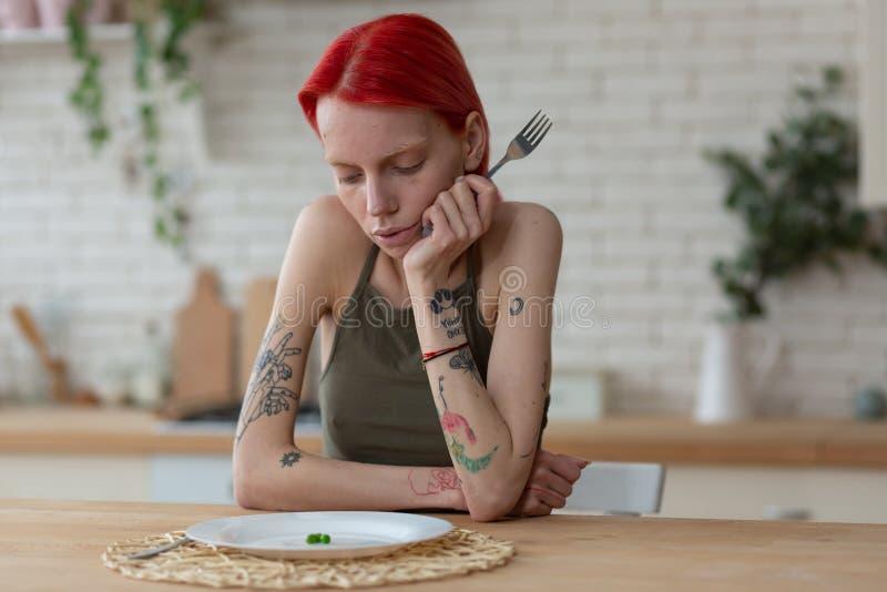Γυναίκα με το δίκρανο εκμετάλλευσης βουλιμίας και εξέταση το πιάτο με τα μπιζέλια στοκ εικόνες με δικαίωμα ελεύθερης χρήσης