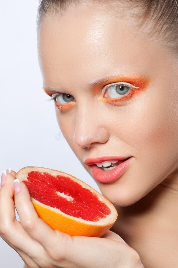 Γυναίκα με το δημιουργικά makeup και το γκρέιπφρουτ στοκ φωτογραφίες με δικαίωμα ελεύθερης χρήσης