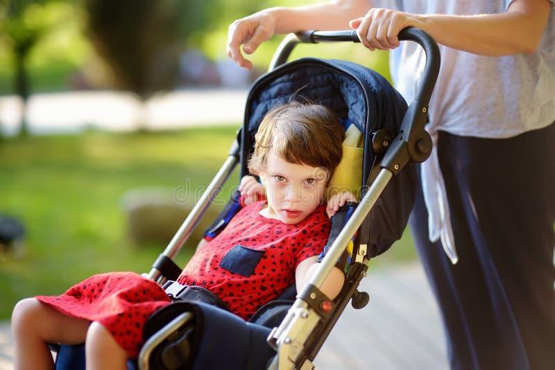 Γυναίκα με το με ειδικές ανάγκες κορίτσι σε μια αναπηρική καρέκλα που περπατά στο θερινό πάρκο στοκ φωτογραφία