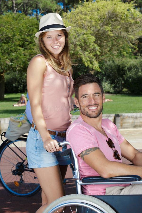 Γυναίκα με το με ειδικές ανάγκες συνεργάτη στην αναπηρική καρέκλα στο πάρκο στοκ εικόνα