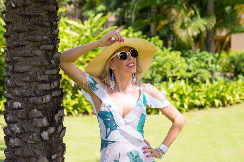 Γυναίκα με το θερινό καπέλο και γυαλιά ηλίου που στέκονται κάτω από το φοίνικα στοκ φωτογραφίες
