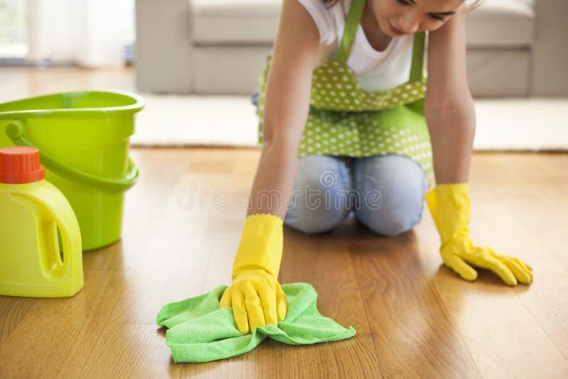 Γυναίκα με το καθαρίζοντας πάτωμα υφασμάτων στο σπίτι στοκ εικόνες