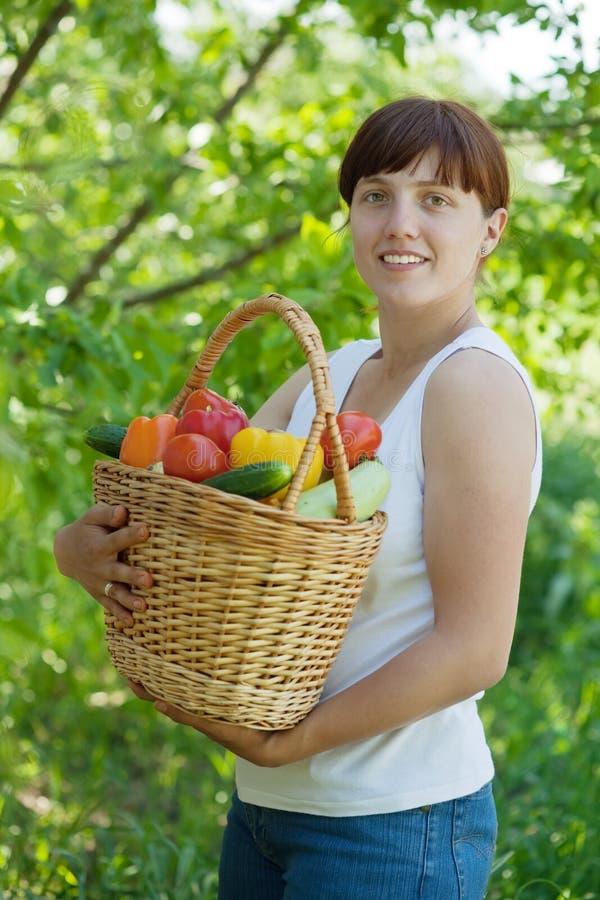 Γυναίκα με το καλάθι των συγκομισμένων λαχανικών στοκ εικόνες