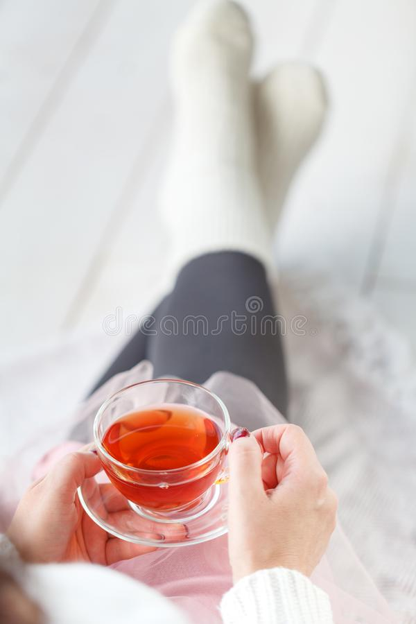 Γυναίκα με το καρό υπολοίπου τσαγιού φλυτζανιών, πόδι με τις άσπρες κάλτσες στοκ φωτογραφίες