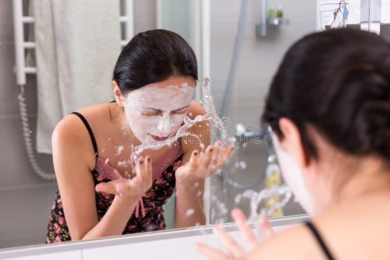 Γυναίκα με το καλλυντικό νερό ψεκασμού μασκών στο πρόσωπό της που στέκεται μέσα στοκ φωτογραφία