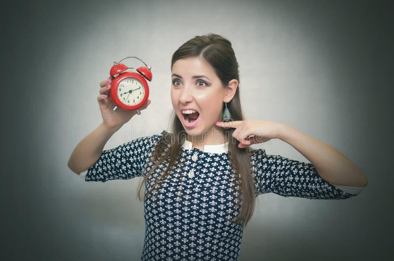 γυναίκα με το κόκκινο ξυπνητήριη oversleep Αργά στην εργασία ή το σχολικό μάθημα στοκ εικόνα