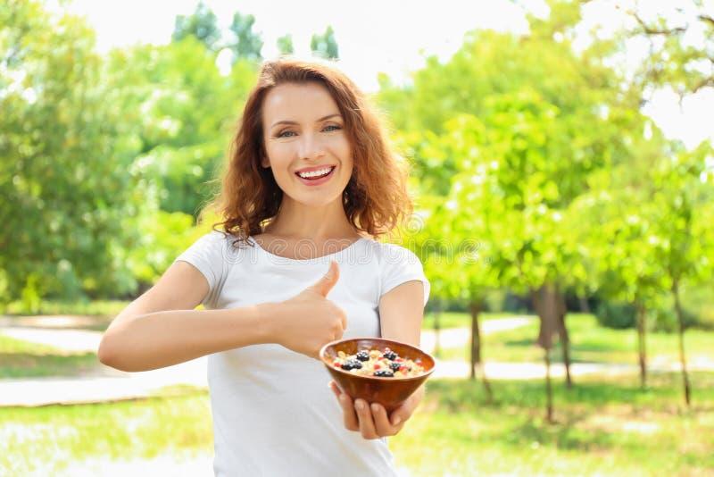 Γυναίκα με το κύπελλο νόστιμο oatmeal που παρουσιάζει αντίχειρας-επάνω στη χειρονομία υπαίθρια στοκ εικόνες