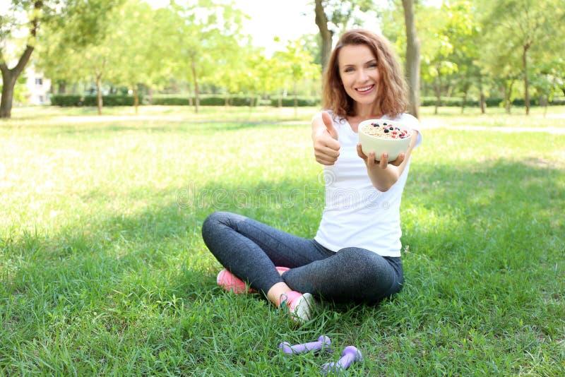 Γυναίκα με το κύπελλο νόστιμο oatmeal που παρουσιάζει αντίχειρας-επάνω στη χειρονομία υπαίθρια στοκ εικόνες με δικαίωμα ελεύθερης χρήσης