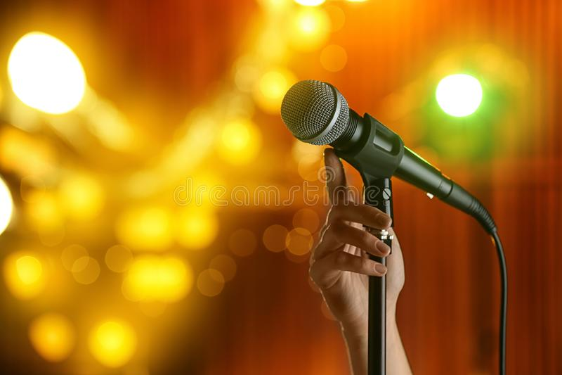 Γυναίκα με το μικρόφωνο ενάντια στα εορταστικά φω'τα, κινηματογράφηση σε πρώτο πλάνο στοκ εικόνες