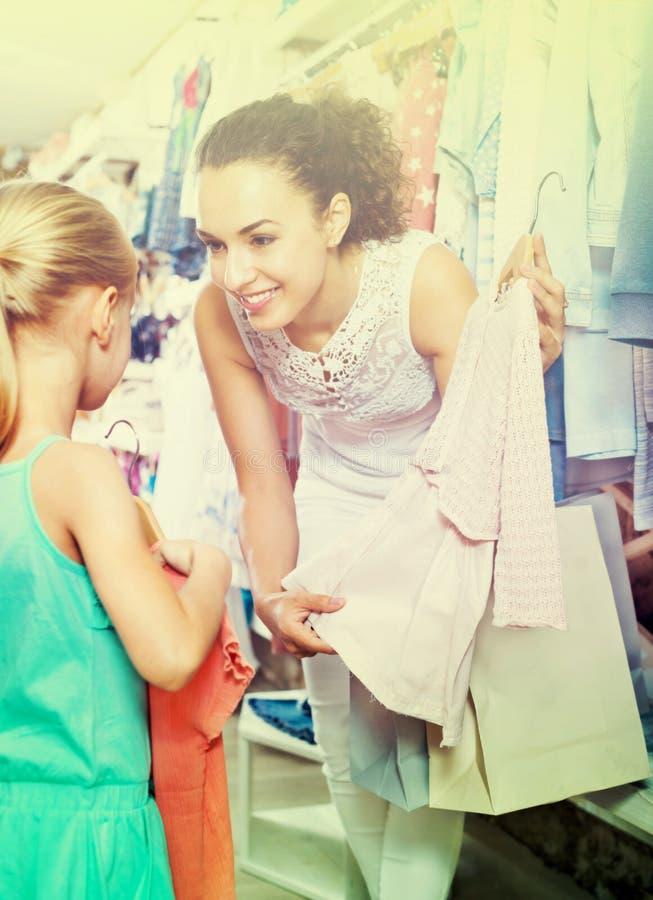 Γυναίκα με το μικρό κορίτσι που επιλέγει τα ρόδινα ενδύματα στοκ εικόνες
