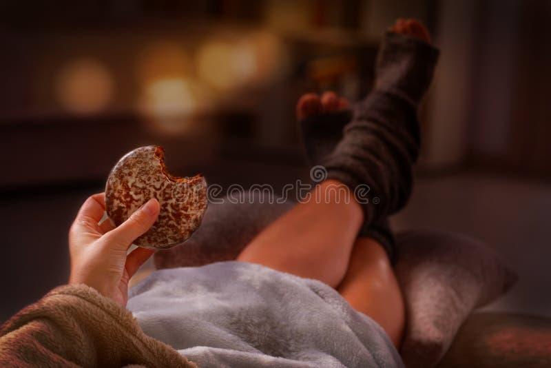 Γυναίκα με το μπισκότο που βρίσκεται στον καναπέ στοκ φωτογραφία με δικαίωμα ελεύθερης χρήσης