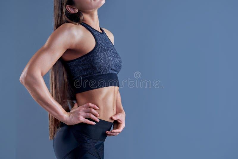 Γυναίκα με το μυϊκό σώμα στον αθλητισμό που ντύνει τη χαλάρωση μετά από το workout, πόσιμο νερό στο ρόδινο υπόβαθρο Εικόνα με το  στοκ φωτογραφίες