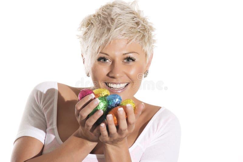 Γυναίκα με το ξανθό αυγό Πάσχας λαγουδάκι σοκολάτας εκμετάλλευσης τρίχας στοκ φωτογραφίες