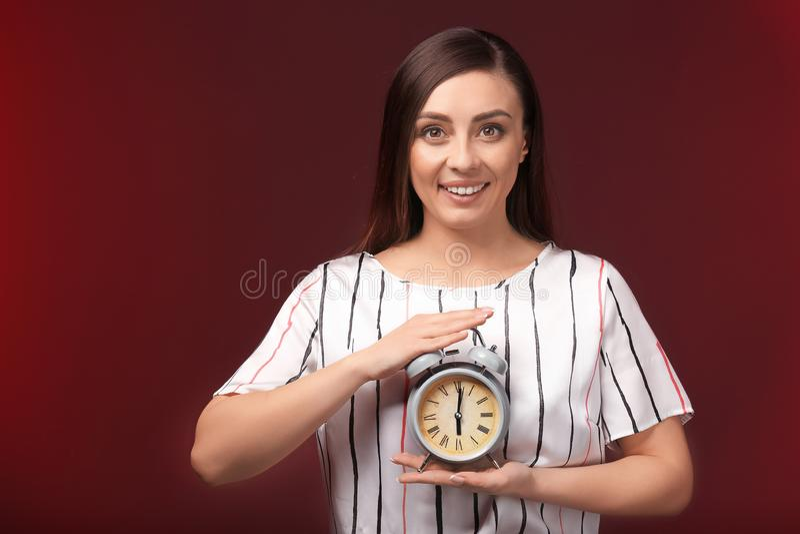 Γυναίκα με το ξυπνητήρι στο υπόβαθρο χρώματος E στοκ φωτογραφίες με δικαίωμα ελεύθερης χρήσης