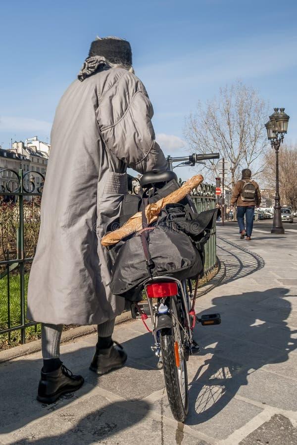 Γυναίκα με το ποδήλατο και χαρακτηριστικό γαλλικό baguette στις οδούς του κεντρικού Παρισιού, Γαλλία στοκ φωτογραφίες