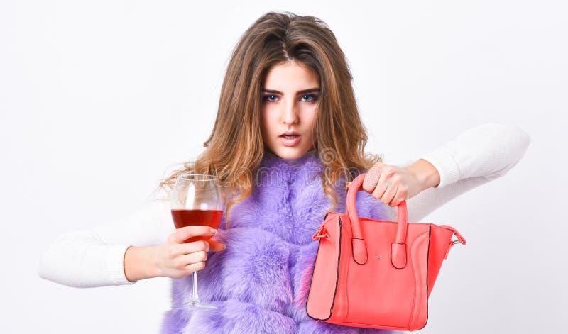 Γυναίκα με το ποτήρι λαβής τσαντών του κρασιού Φανέλλα γουνών μόδας ένδυσης κοριτσιών θέτοντας με την τσάντα Έννοια καταστημάτων  στοκ φωτογραφία
