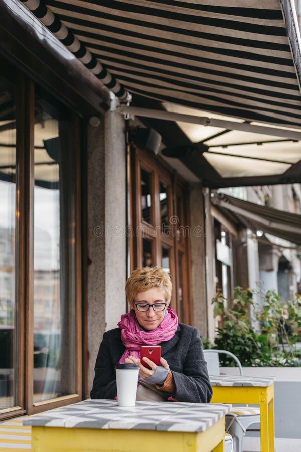 Γυναίκα με το ποτό και το smartphone στοκ φωτογραφία με δικαίωμα ελεύθερης χρήσης