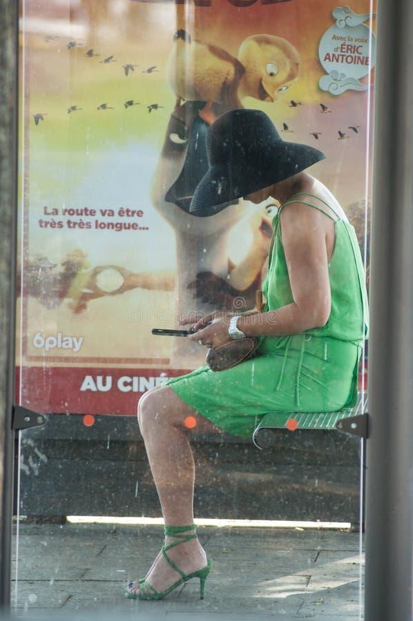Γυναίκα με το πράσινα φόρεμα, το καπέλο και το smartphone που περιμένει στη στάση λεωφορείου κοντά στο σταθμό τρένου στοκ φωτογραφίες