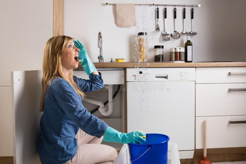 Γυναίκα με το πρόβλημα διαρροής στην κουζίνα στοκ εικόνες