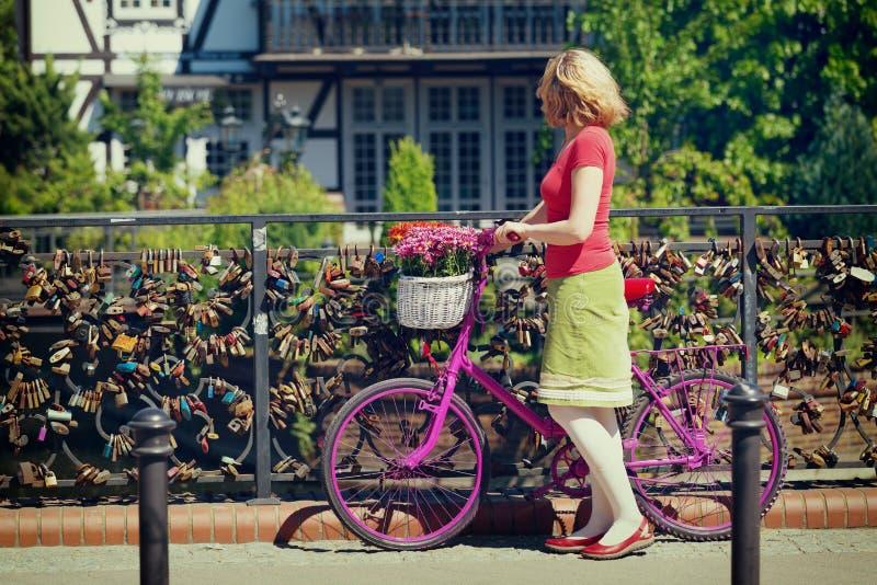 Γυναίκα με το ρόδινο ποδήλατο που στέκεται στη γέφυρα της αγάπης στοκ εικόνες