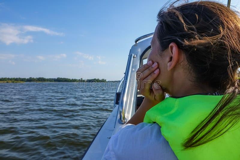 Γυναίκα με το σακάκι ζωής σε μια βάρκα που κοιτάζει έξω πέρα από τον ωκεανό στοκ εικόνα με δικαίωμα ελεύθερης χρήσης