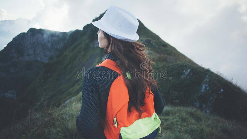 Γυναίκα με το σακίδιο πλάτης και το άσπρο καπέλο που ταξιδεύουν κατά μήκος των ομιχλωδών και νεφελωδών βουνών στοκ φωτογραφίες με δικαίωμα ελεύθερης χρήσης