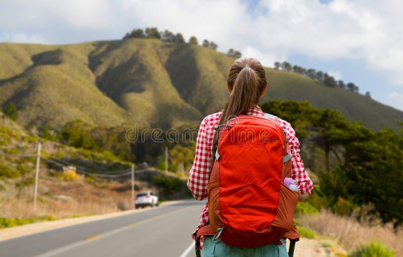 Γυναίκα με το σακίδιο πλάτης που ταξιδεύει πέρα από τους μεγάλους λόφους sur στοκ εικόνα