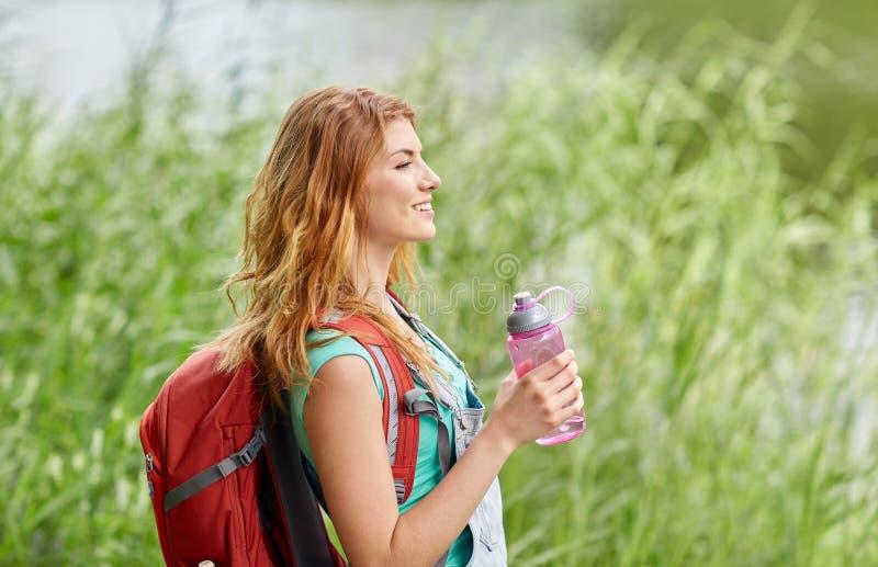Γυναίκα με το σακίδιο πλάτης και την πεζοπορία μπουκαλιών νερό στοκ εικόνες