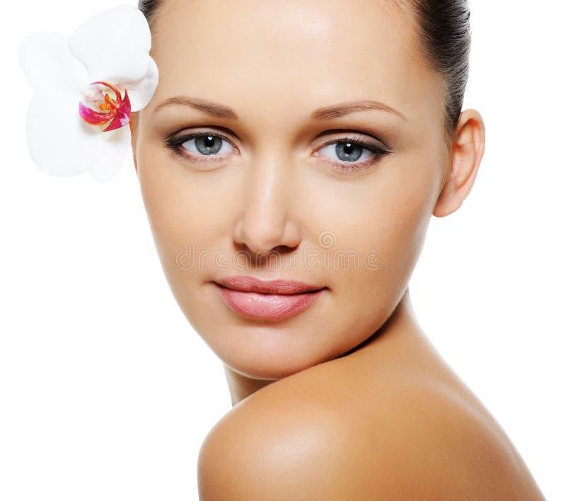 Γυναίκα με το σαφές δέρμα και λουλούδι κοντά στα μάτια της στοκ φωτογραφία με δικαίωμα ελεύθερης χρήσης