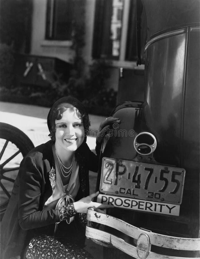 Γυναίκα με το σημάδι ευημερίας στον προφυλακτήρα αυτοκινήτων (όλα τα πρόσωπα που απεικονίζονται δεν ζουν περισσότερο και κανένα κ στοκ φωτογραφίες με δικαίωμα ελεύθερης χρήσης