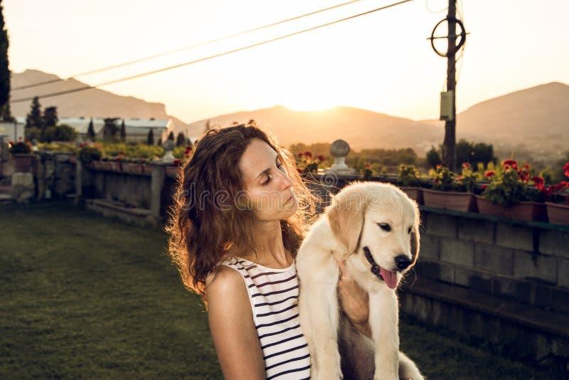 Γυναίκα με το σκυλί κουταβιών στο ηλιοβασίλεμα στοκ φωτογραφία με δικαίωμα ελεύθερης χρήσης