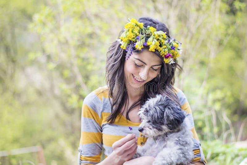 Γυναίκα με το στεφάνι που αγκαλιάζει την λίγο σκυλί στοκ φωτογραφία με δικαίωμα ελεύθερης χρήσης