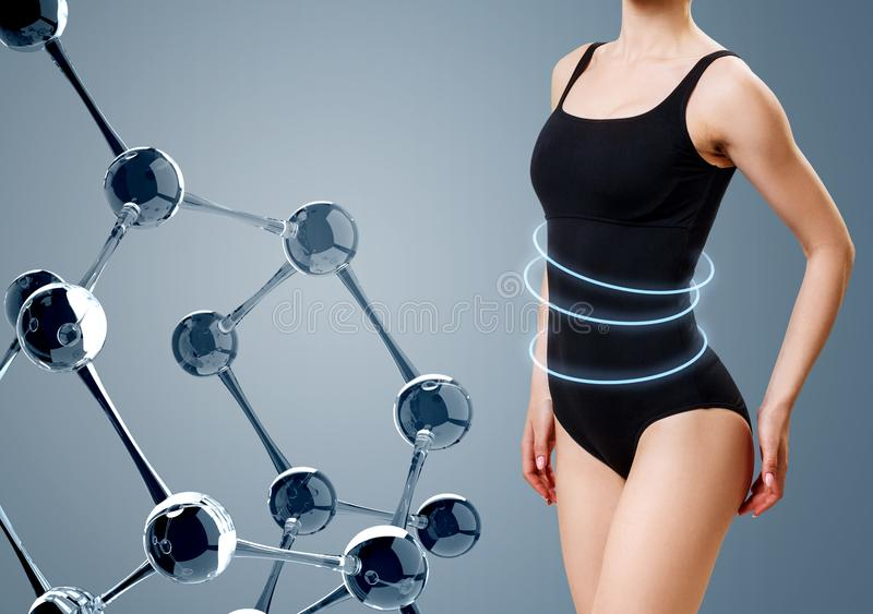 Γυναίκα με το τέλειο σώμα στο μαγιό κοντά στην αλυσίδα μορίων γυαλιού στοκ φωτογραφία