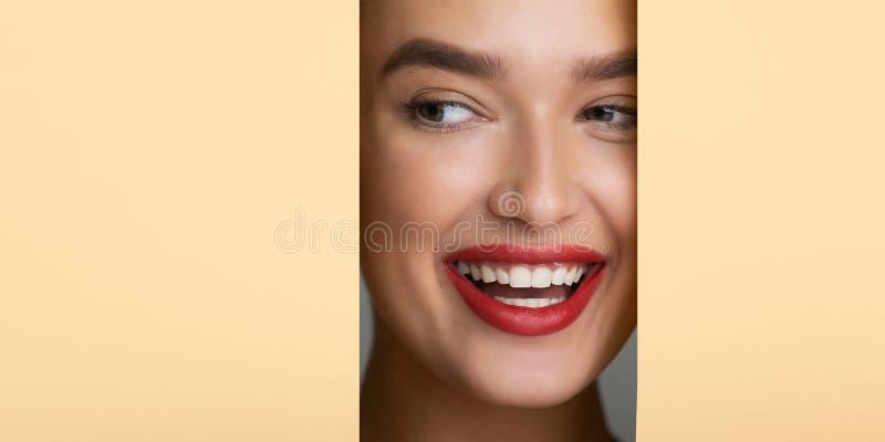 Γυναίκα με το τέλειο χαμόγελο και τα κόκκινα χείλια που εξετάζει την τρύπα στοκ φωτογραφία με δικαίωμα ελεύθερης χρήσης