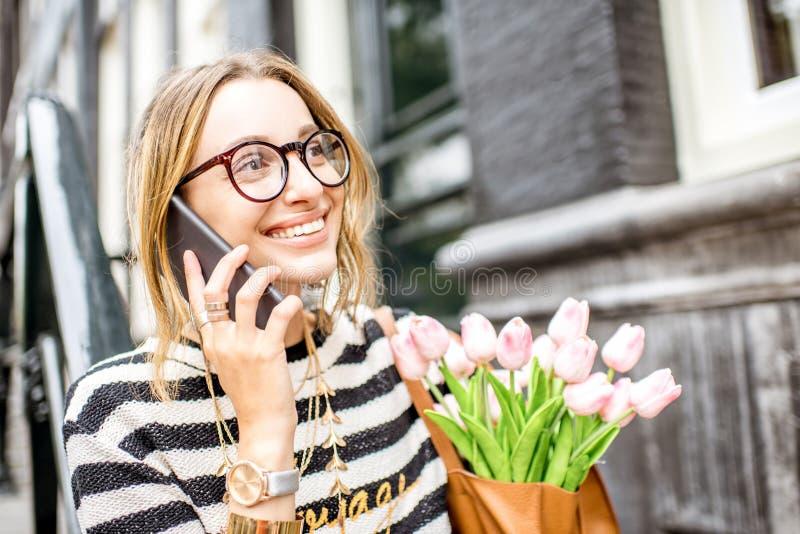 Γυναίκα με το τηλέφωνο και λουλούδια κοντά στο κτήριο στοκ εικόνες
